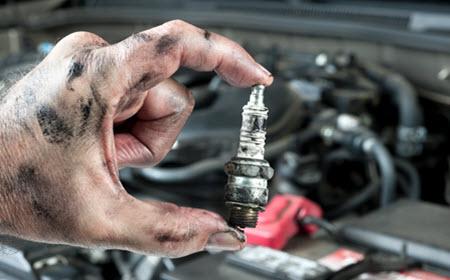 Audi Mechanic Holding Worn Spark Plugs
